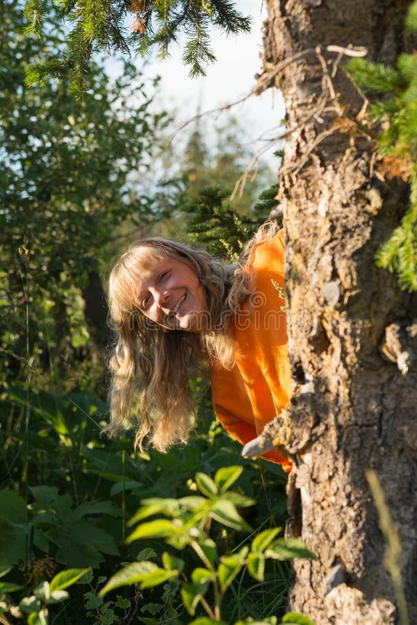 A laughing white middle-aged woman peeks out from behind a tree in the forest. stock images