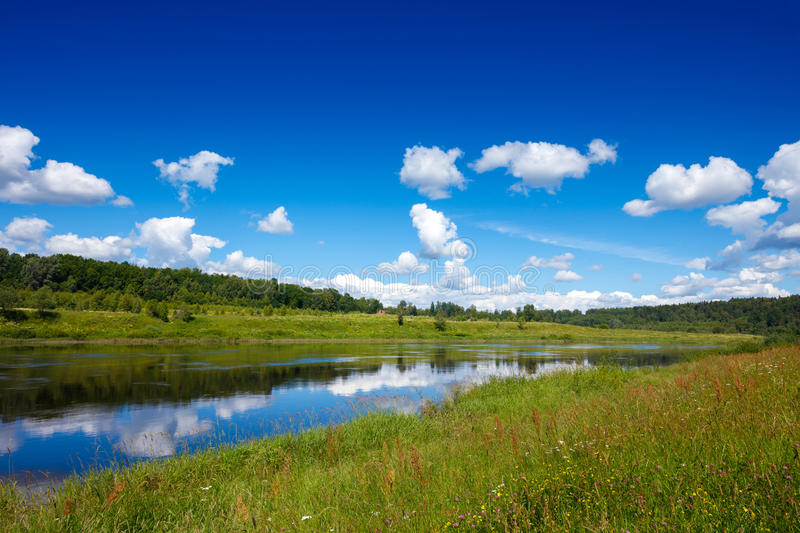 Summer landscape with meadows, forest, river, blue sky and reflection of white clouds.  stock image