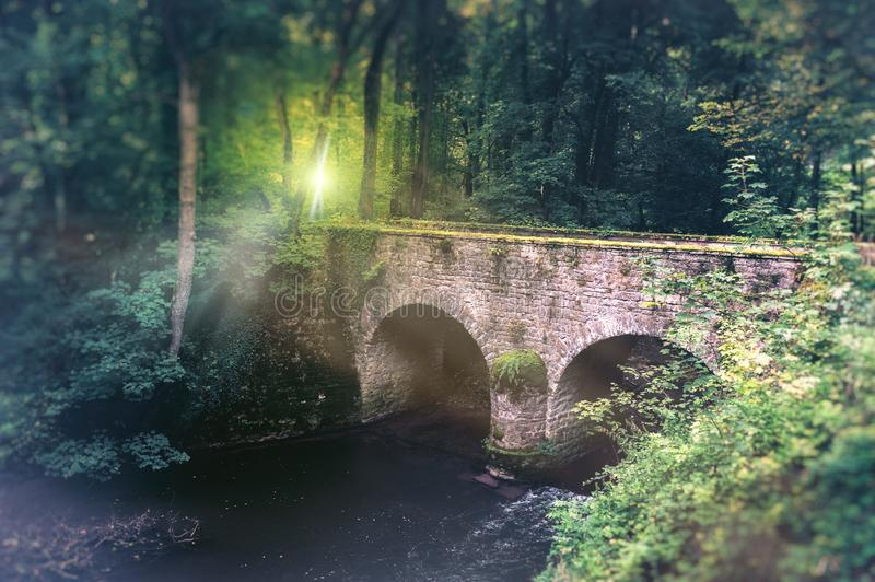 Summer landscape with old cobblestone bridge and small river. Na. Summer landscape with old cobblestone bridge and small forest river. Nature background royalty free stock photo