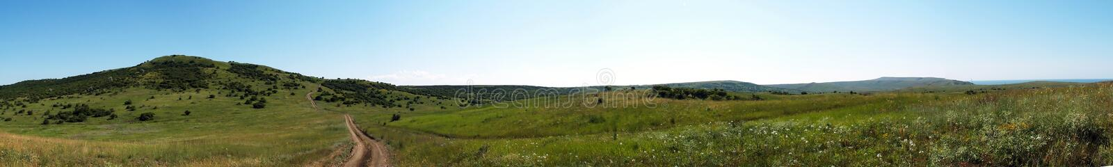 Summer Landscape Panorama. Panorama of summer field with lonely dirt road going to horizon. Foreground have various wild flowers and distant hill covered with stock photos