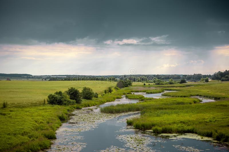 Summer landscape with a river and thunderclouds, open countryside_. Summer landscape with a river and thunderclouds, open countrye royalty free stock photography