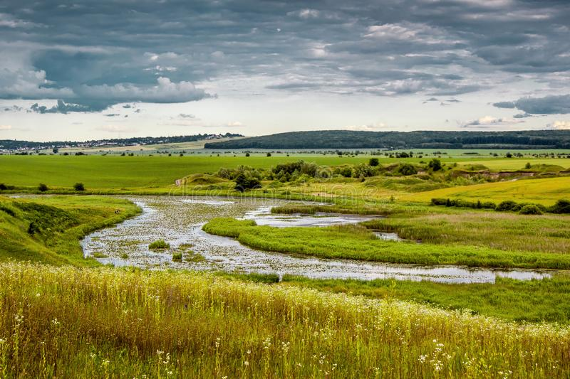 Summer landscape with a river and thunderclouds, open countryside_. Summer landscape with a river and thunderclouds, open countrye stock photo