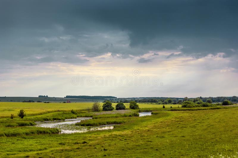 Summer landscape with a river and thunderclouds, open countryside_. Summer landscape with a river and thunderclouds, open countryside royalty free stock photo