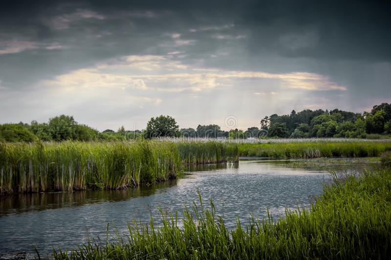 Summer landscape with a river and thunderclouds, open countryside_. Summer landscape with a river and thunderclouds, open countrye stock photos