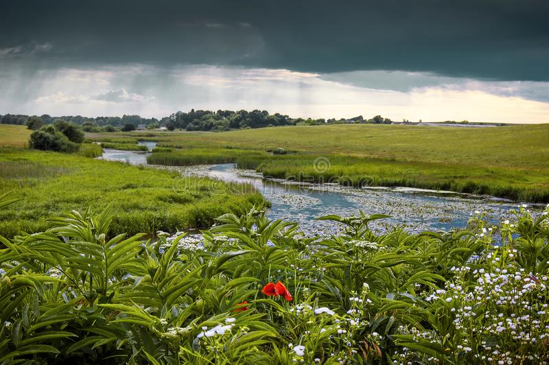 Summer landscape with a river and thunderclouds, open countryside_. Summer landscape with a river and thunderclouds, open countryside stock photo