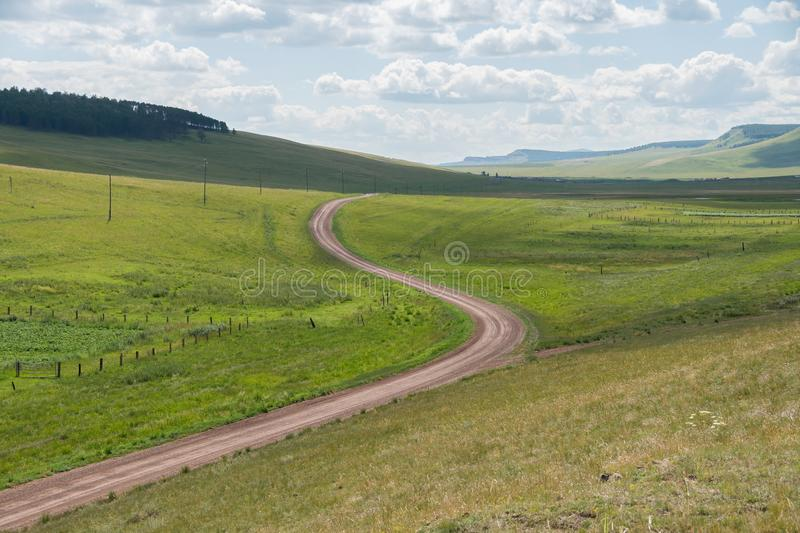 The rural dirt road goes beyond the horizon along the green steppe. stock photo