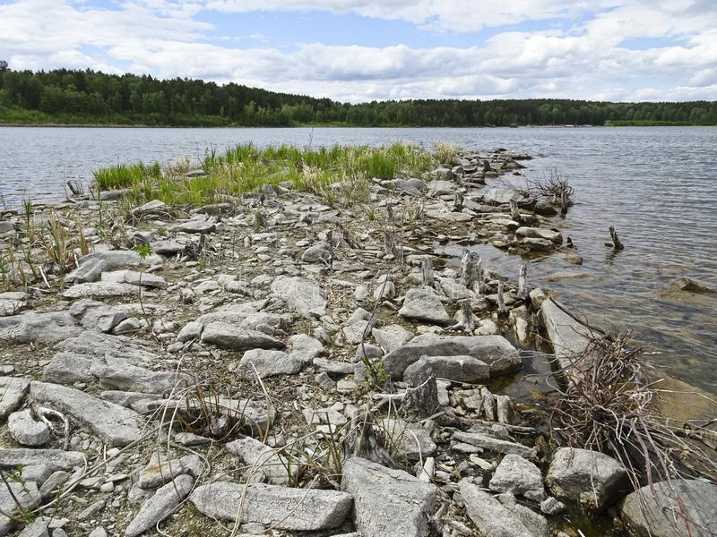 Summer landscape: stony shore of a forest lake in cloudy weather. There are many large stones on the shore stock photo