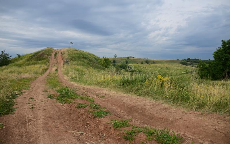 Summer landscape with unpaved roads among high green hills stock photos
