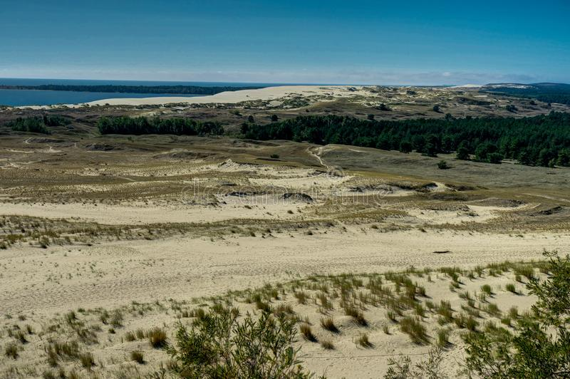 Summer landscape with white sand dunes, bushes and sky. Curonian Spit, Baltic sea. UNESCO World Heritage Site. royalty free stock images