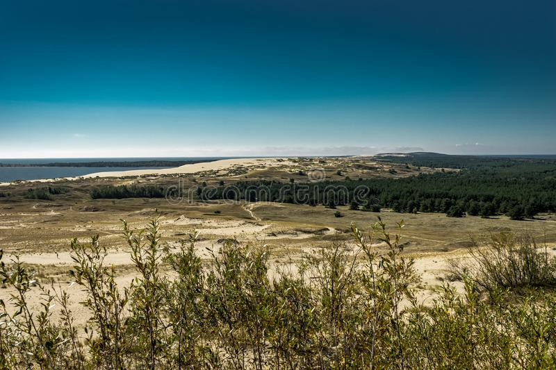 Summer landscape with white sand dunes, bushes and sky. Curonian Spit, Baltic sea. UNESCO World Heritage Site. stock image