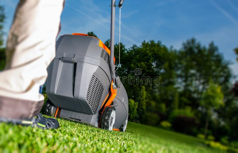 Summer Lawn Mowing. And Backyard Landscaping. Men with Grass Mower stock photo
