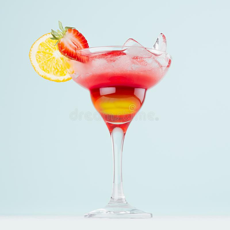 Summer layered drink with red and yellow liquor, orange slice, strawberry, ice cubes in wineglass on pastel mint background. Summer layered drink with red and royalty free stock images