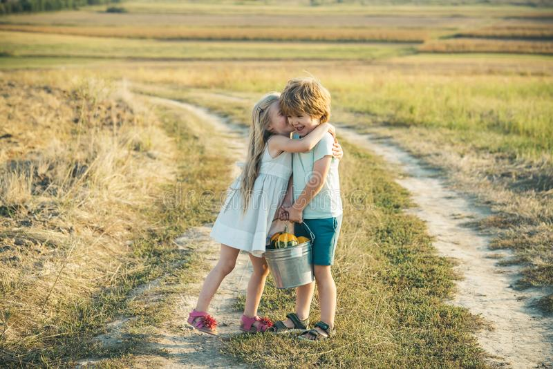 Summer leisure. Happy kid on summer field. Cute little farmers - sister and brother working with spud on spring field. Farming and agriculture cultivation. Two royalty free stock photo