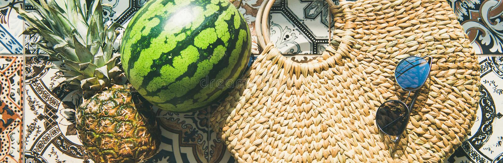 Summer lifestyle background with fruits and straw bag, wide composition. Summer lifestyle background. Flat-lay of summer fruit pineapple and watermelon, straw royalty free stock image
