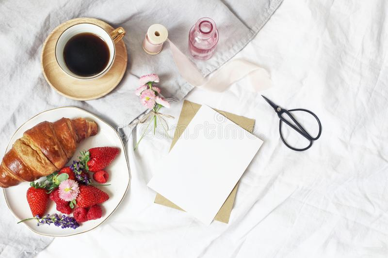 Summer lifestyle composition. Blank greeting card mockup scene with cup of coffee, croissant pastry, strawberries. Raspberries and daisy flowers. Breakfast in royalty free stock images