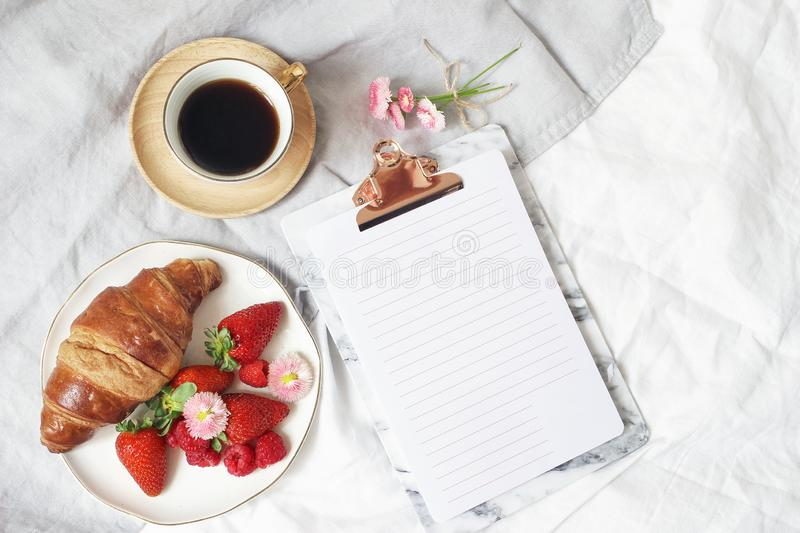Summer lifestyle composition. Blank paper in clipboard mockup with cup of coffee, croissant pastry, strawberries royalty free stock image