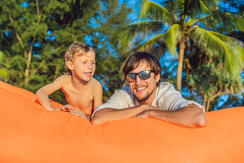 Summer lifestyle portrait of father and son sitting on the orange inflatable sofa on the beach of tropical island royalty free stock photo