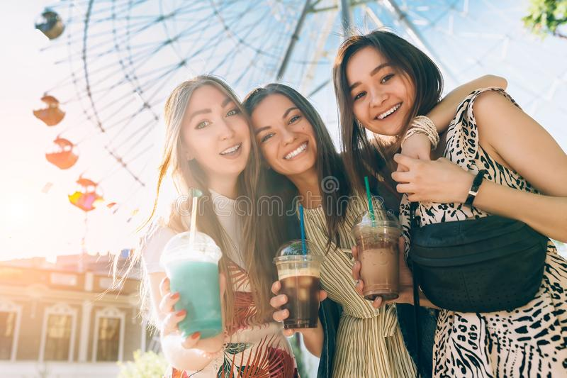 Summer lifestyle portrait multiracial women enjoy nice day, holding glasses of milkshakes. Happy friends inin front of stock photos