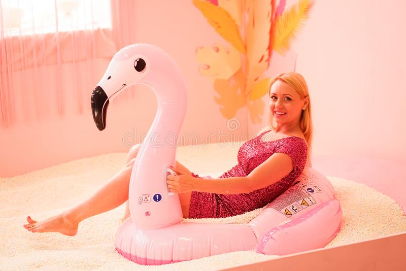 Summer lifestyle portrait of pretty girl having fun on air mattress in the pool with polyfoam balls stock images