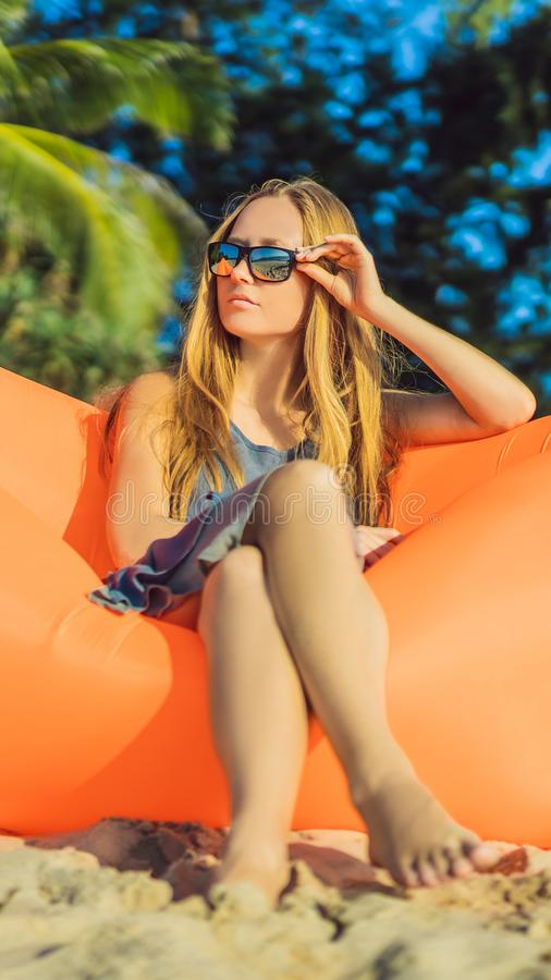 Summer lifestyle portrait of pretty girl sitting on the orange inflatable sofa on the beach of tropical island. Relaxing stock photography
