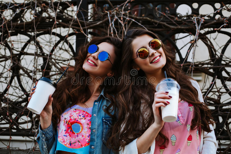 Summer lifestyle portrait of two hipster stylish women with fit body, wearing denim outfit and vintage sunglasses royalty free stock photography
