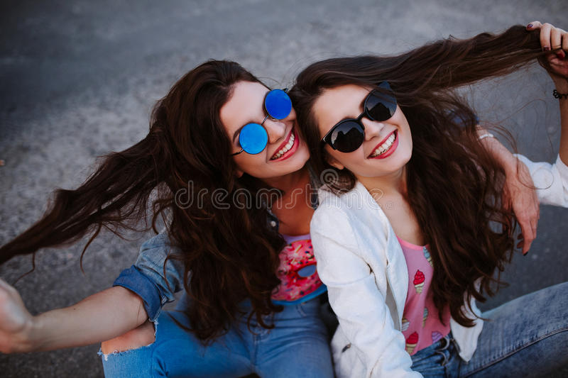 Summer lifestyle portrait of two hipster stylish women with fit body, wearing denim outfit and vintage sunglasses royalty free stock image