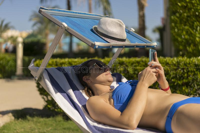 Summer lifestyle portrait of young stunning woman lying on the sunbed on the beach of the tropical island and uses smartphone. Young white woman lying on blue stock images
