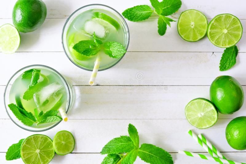 Summer limeade, top view frame on a white wood background. Sweet summer limeade. Top view frame with limes and mint on a white wood background stock photography