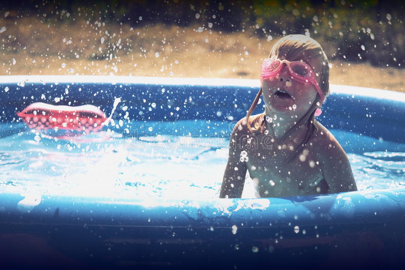 Summer little girl playing in the pool. Blond baby girl playing in a blue swimming pool stock photography