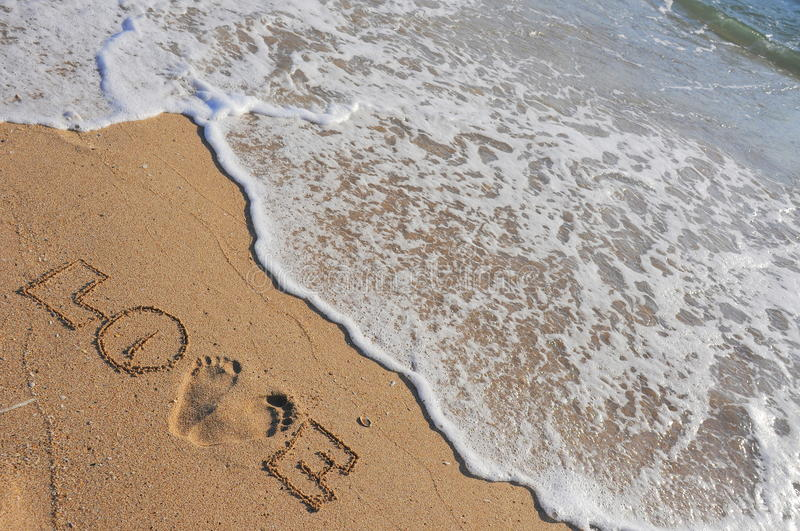 Summer love. A love statement written on the hot summer beach sand about to be cooled down by the foamy wave stock photos