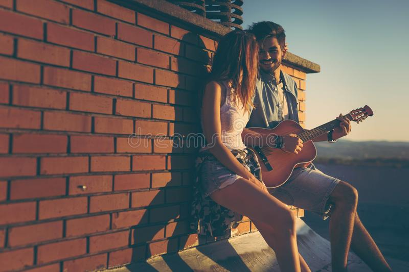 Summer love. Couple in love hanging out at a rooftop party, leaning against a brick wall ; guy playing the guitar and singing stock image