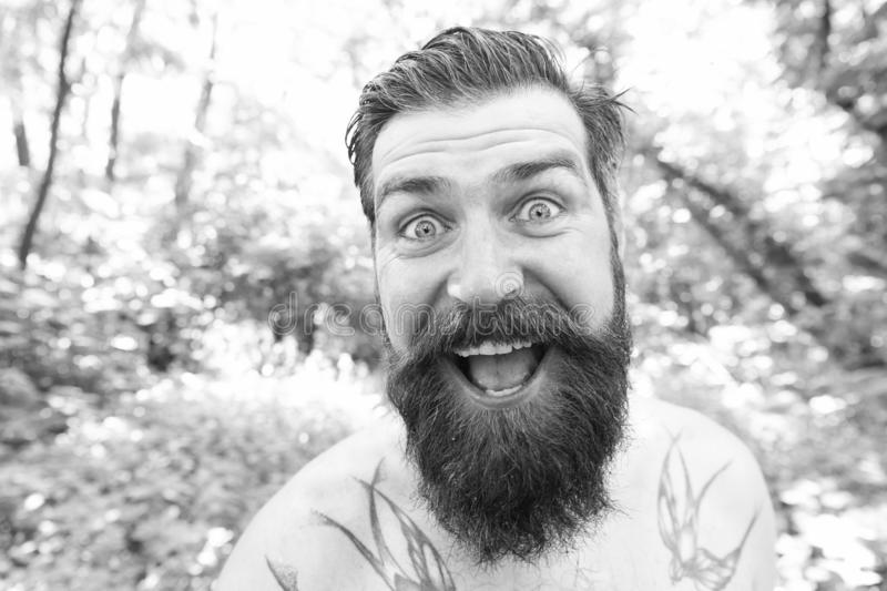 Summer madness. Man cheerful bearded hipster taking selfie in wild nature. Guy crazy emotional face surviving in hot royalty free stock photo