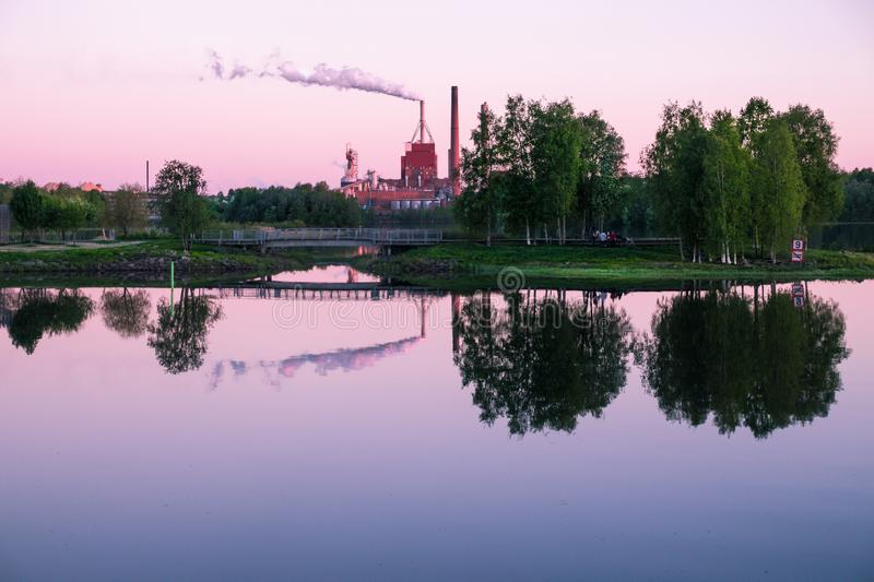 Summer Midnight in Oulu. Reflections of trees and industry over a river in Oulu, Finland, in a summer night