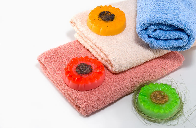 Summer mood for a bathroom. Handmade soap in the shape of flowers among the towels royalty free stock photography