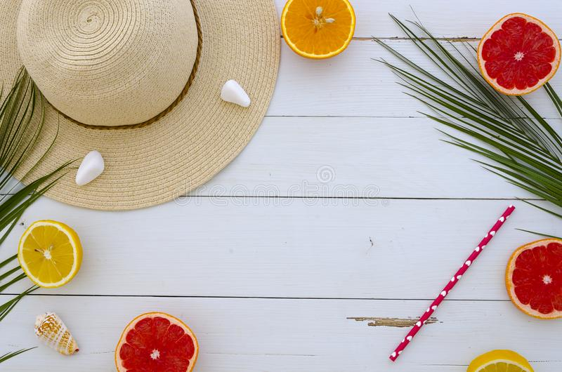 Summer mood juicy lobes of lemon, orange and grapefruit, fresh citrus and sun hat. Time to drink cocktails. Hand royalty free stock photography