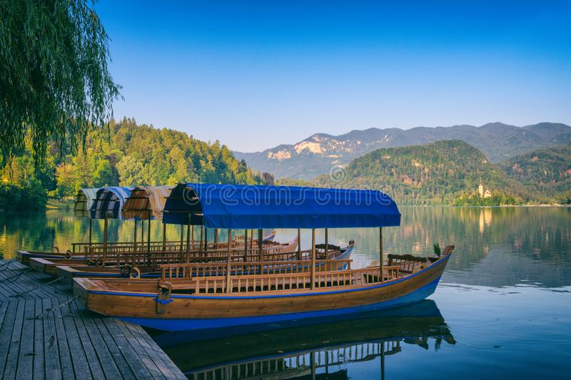 Summer morning on the alpine lake Bled, pleasure boats, green mountains and blue sky nature landscape, Slovenia stock images