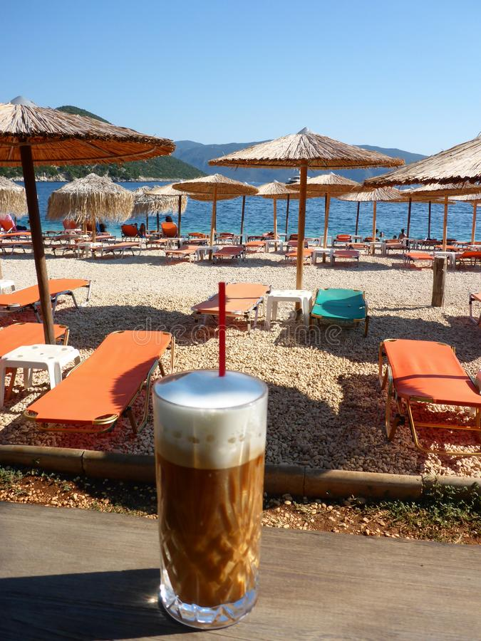 Summer morning with freddo cappuccino greek cold coffee drink on the backgraund straw umbrellas and sunbeds of Antisamos beach, royalty free stock photos