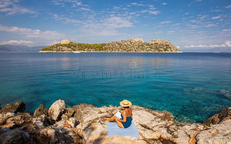 Summer morning young woman sunbathing and reading on a rocky beach of Agistri island, Aponissos bay, Saronic Gulf, Greece. Horizontal royalty free stock photo