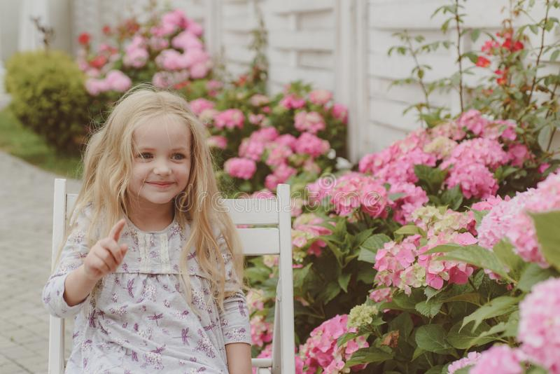 Summer. Mothers or womens day. Little girl at blooming flower. Childrens day. Small baby girl. Spring flowers. Childhood royalty free stock image