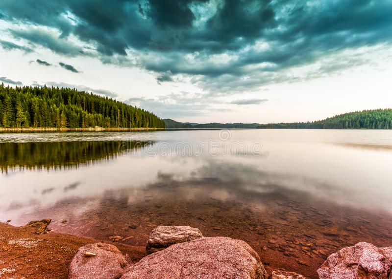 Summer mountain lake theme with cloudy blue sky stock image