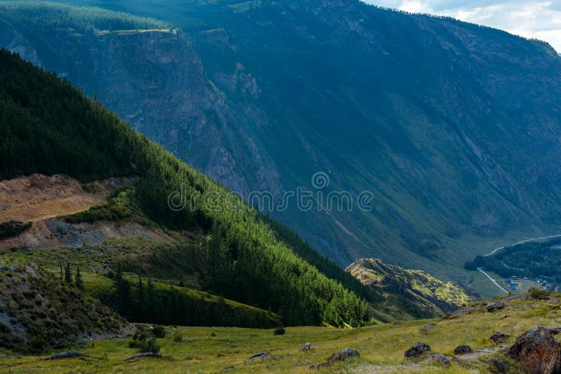 Summer mountain landscape with green trees on slope and the  curve road at the foot of the rock. Spectacular view from meadow stock photography