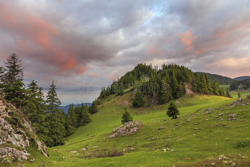 Summer mountain meadow red clouds. Sunrise over summer green mountain meadow red clouds royalty free stock photography