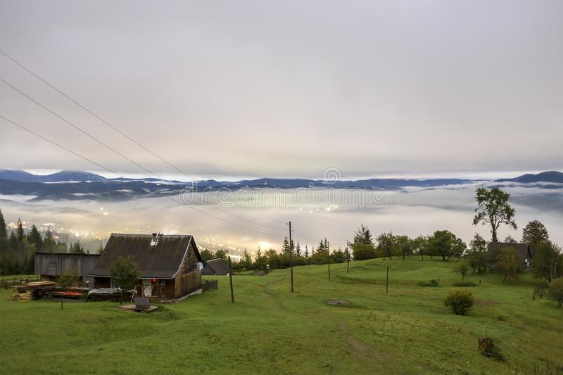 Summer mountain panorama. Small wooden house cottage and barn on green mountain valley on bright foggy sky, clouds and mountain stock image