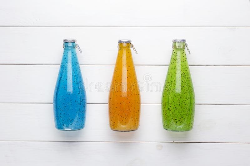 Summer multicolored refreshing drink in the bottle with chia and basil seed and fruit juice on white wooden background. stock photos