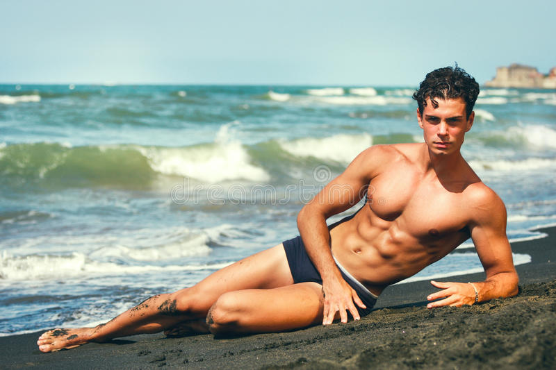 Summer. Muscular guy lying on his side. By the sea. Sculptural body. A beautiful young Italian man with a fabulous body lying on the sand by the sea. Abdominal stock photo