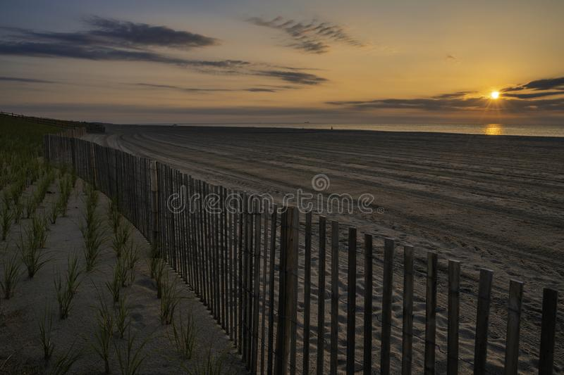 Summer in New Jersey Shore. Beautiful sunrise over Lavallette Beach, New Jersey featuring sand on the foreground and sunny sky on the background stock images