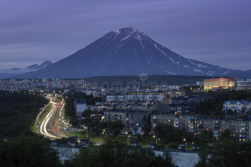 Summer night cityscape driving automobiles on city road on background of volcano. Summer cityscape of Kamchatka Peninsula: night view of urban development of royalty free stock images