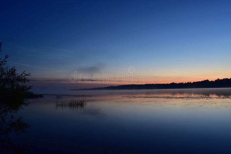 Summer night on the great river, the branches over the water rushes coming stock photography