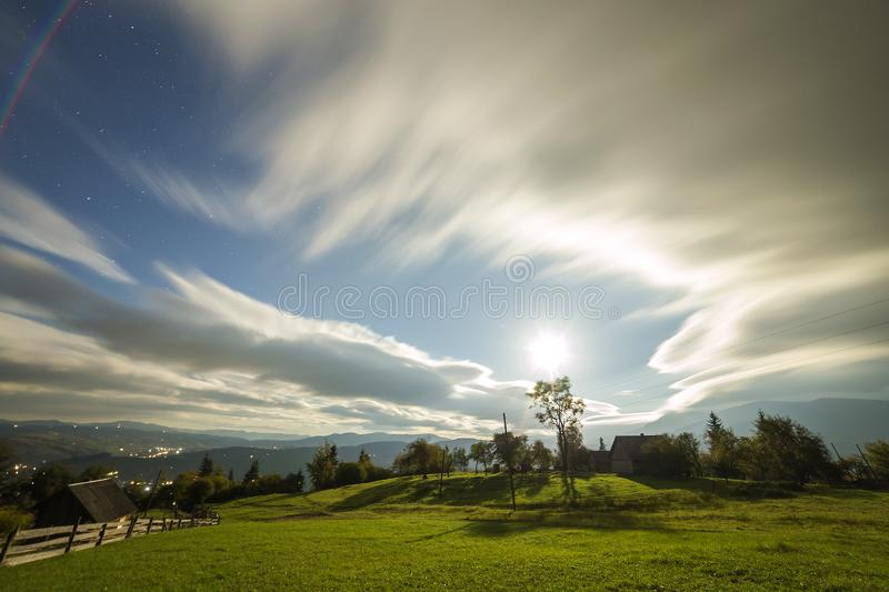 Summer night mountain panorama. Old wooden weathered shepherd huts on green clearing on cloudy evening sky background, bright road royalty free stock images