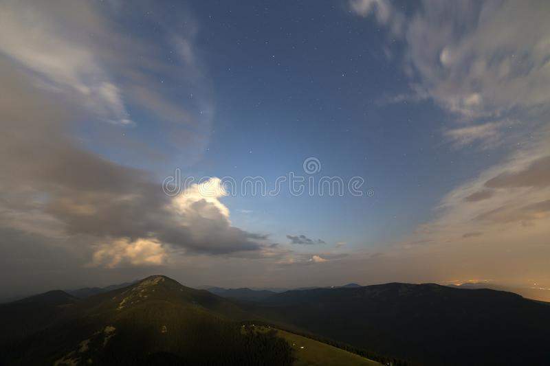Summer night in mountains. Starry dark blue sky and white clouds at sunset over mountain range. Beautiful summer night in mountains. Wide view of starry dark stock photography